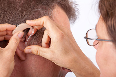 Doctor fitting a senior man patient with hearing aid